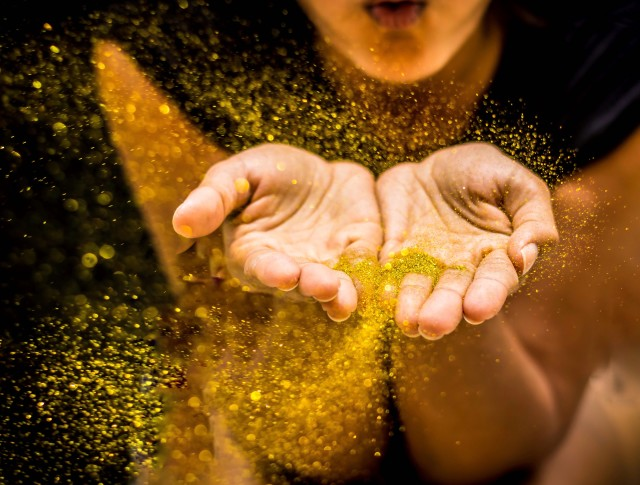 Girl blowing gold confetti / glitter