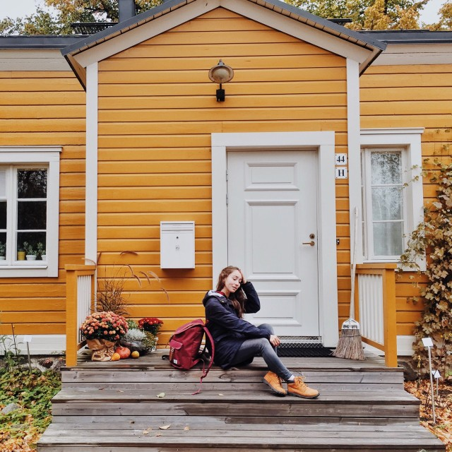 Autumn in the city. The girl is sitting on the porch against an orange wall. Stockholm, Sweden