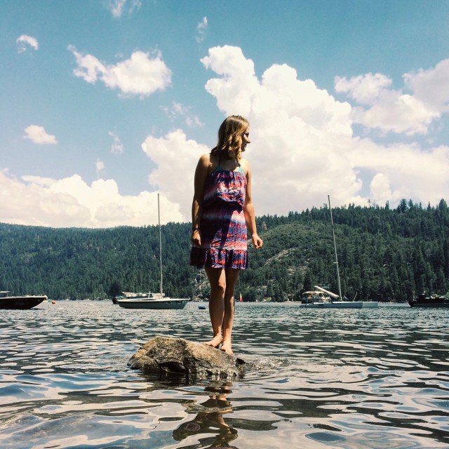 Woman stand on a rock surrounded by water.