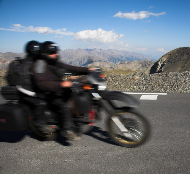 Road trip in the mountains, motorbike and bikers in motion, landscape and horizon, motion blur , high altitude, sunny day, blue sky, copy space