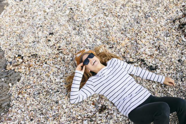 Girl laughing with sunglasses laying at the beach in seashells