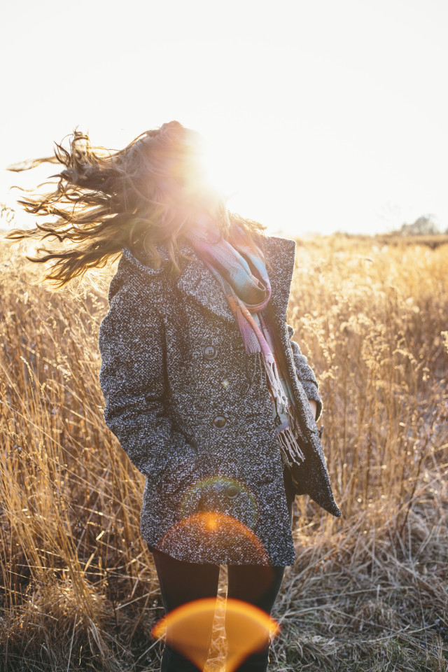 Girl in a field during Fall at sunset shaking hair with sunburst