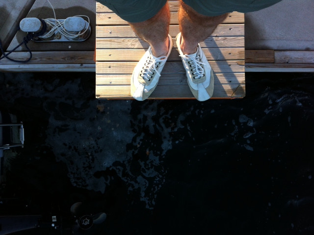 Man' s legs and shoes, before a jump in the sea or getting on board on a sailboat, natural light