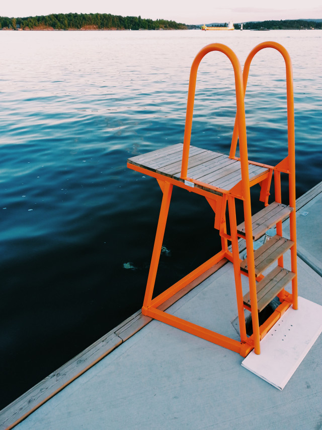 Summertime : before or after the jump ?! Seaside, orange ladder and seat, horizon over the sea, reflections on the water, island, bright, leisure, vacations