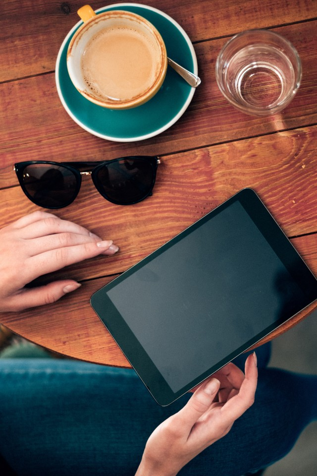 Woman hands holding tablet and drinking coffee