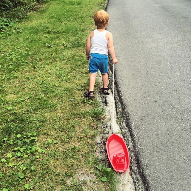 Little boy from behind with a red toy boat.