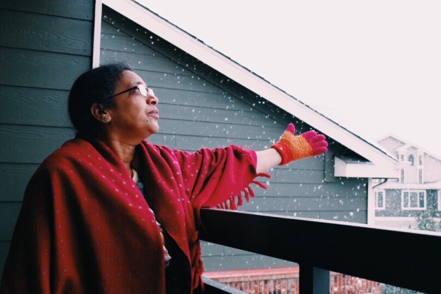 Old woman excited to see snow falling in daylight in Colorado Denver. adults cherishing moments in locked down at home in corona virus pandemic during holidays
