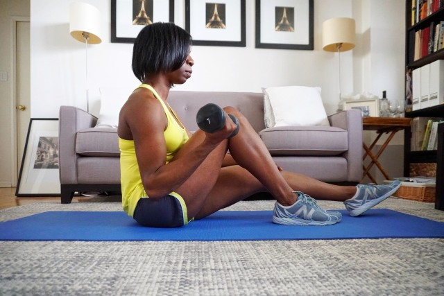 Woman working out at home in bright sportswear and lifting small weights