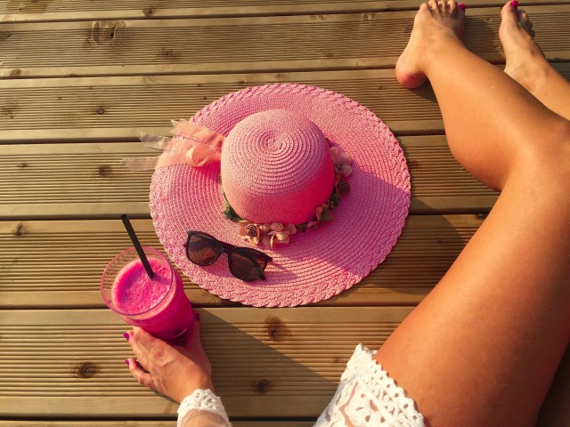 Woman's tanned sexy legs on wooden pontoon with glass of raspberry smoothie and pink summer hat