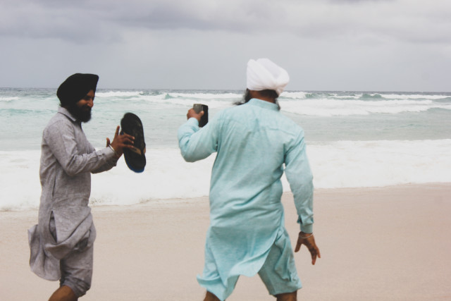Sikh men in traditional clothes, vacationing in Australia, using a mobile phone to take a photo