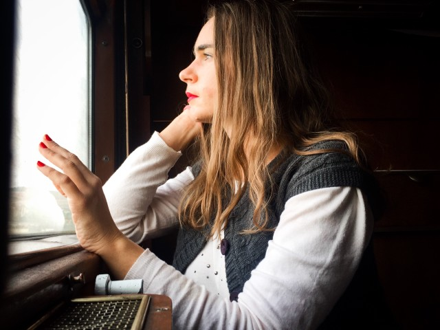 Woman in train sitting next to the window and looking outside with a hand on the window