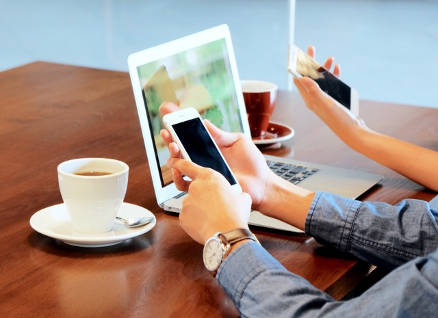 Businessman using smartphone and laptop in cafe