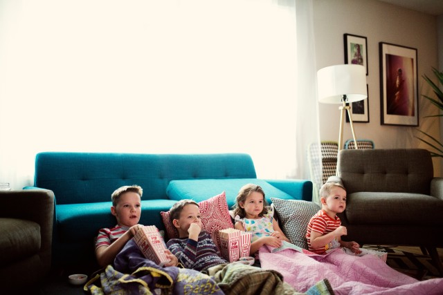 Kids watching a movie at home under a blanket eating popcorn