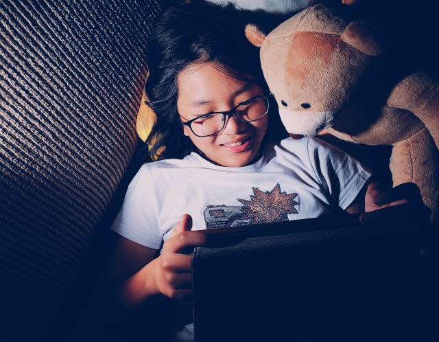 High angle view of a girl laying down on sofa at home and watching video from tablet or making video call with her teddy bear beside her.