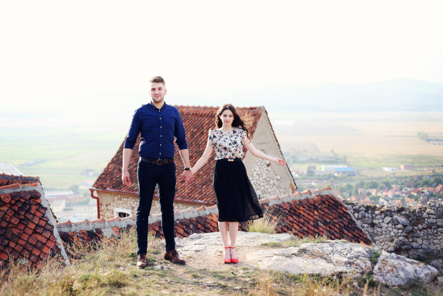 Man and woman holding hands and standing on top of a rock. Medieval village view in the background