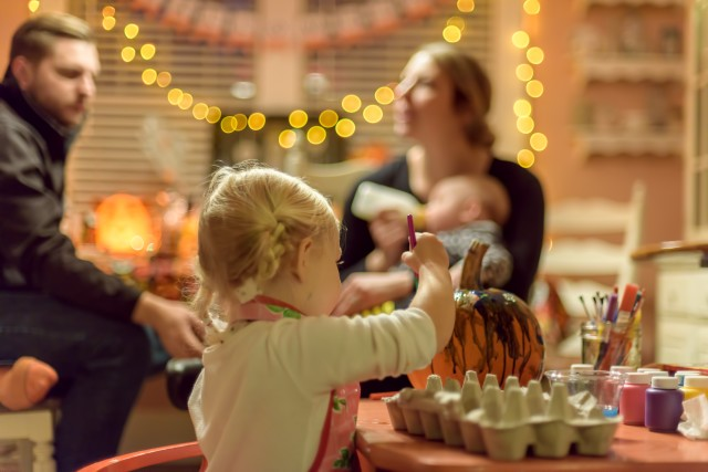 Little girl painting a pumpkin at a Halloween party while adults chat in the background - candid, people, indoors, people at home, family 💲  💫