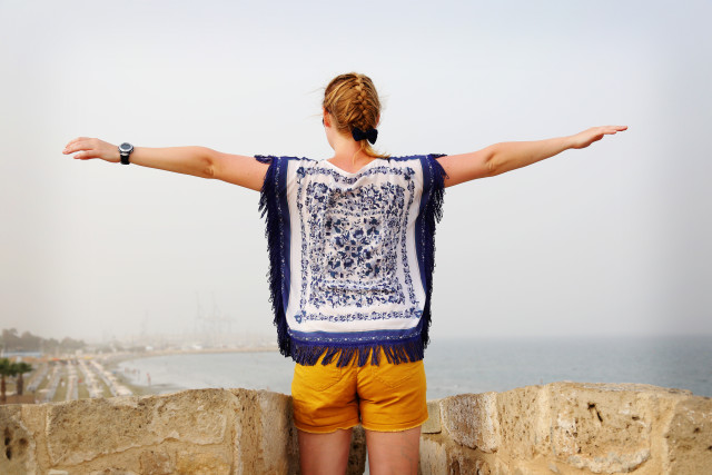 Woman with blonde braided hair looking at the sea, hands wide spread from up a stone wall
