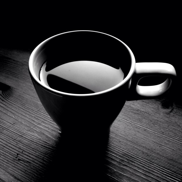 Artistic black and white photograph of coffee mug on the table