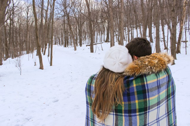 A couple wrapped in a plaid blanket enjoys winter scene in a snowy forest in winter