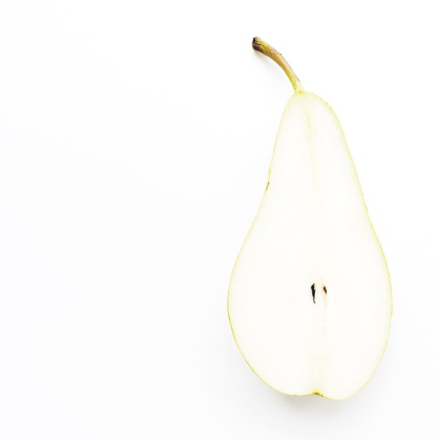 Pear cut in half in minimalist style isolated on white background with copy space