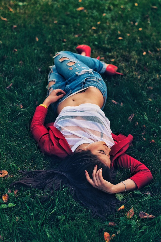 young sexy girl in a transparent T-shirt lies on the green grass