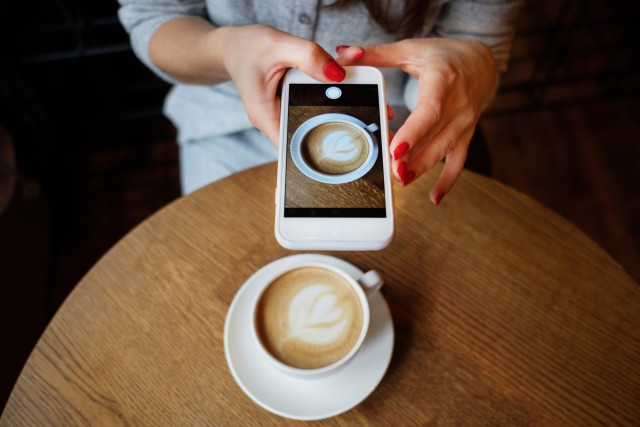 A girl shooting a drink in cafe with the smartphone