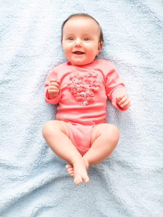 Little baby girl laying on blanket. Portrait of smiling baby happy cute kid