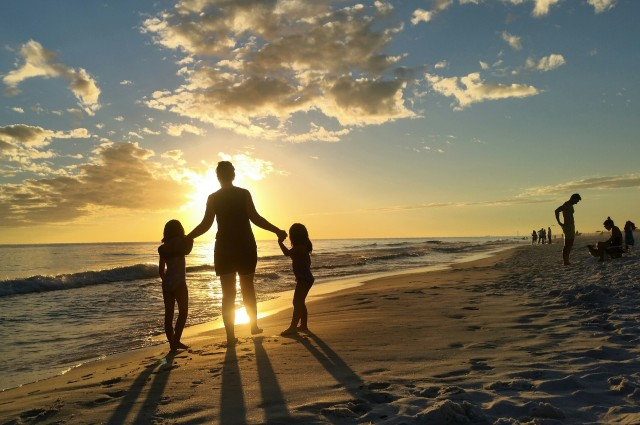 Family walk on the beach at sunset with Mother holding Gen z kids hands as they get nighttime fitness before dinner on gulf coast of florida on seashore  of sandy beach.