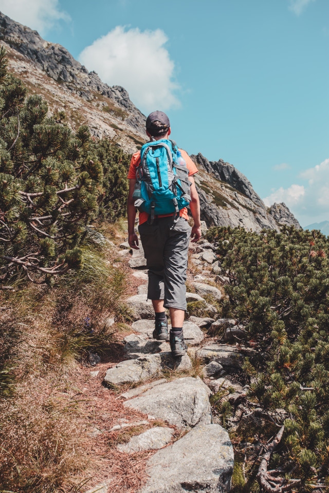 Man hiking in mountains. Summer vacation trip. Backpacker spending time actively. Boy hiking in the mountains