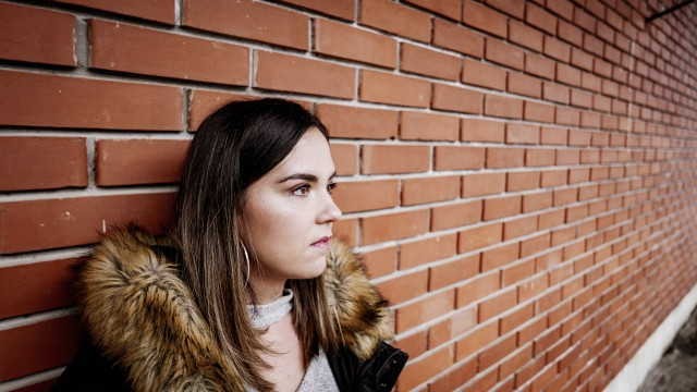 Urban portrait of a young woman leaning on brick wall. Young millennial in a winter jacket.