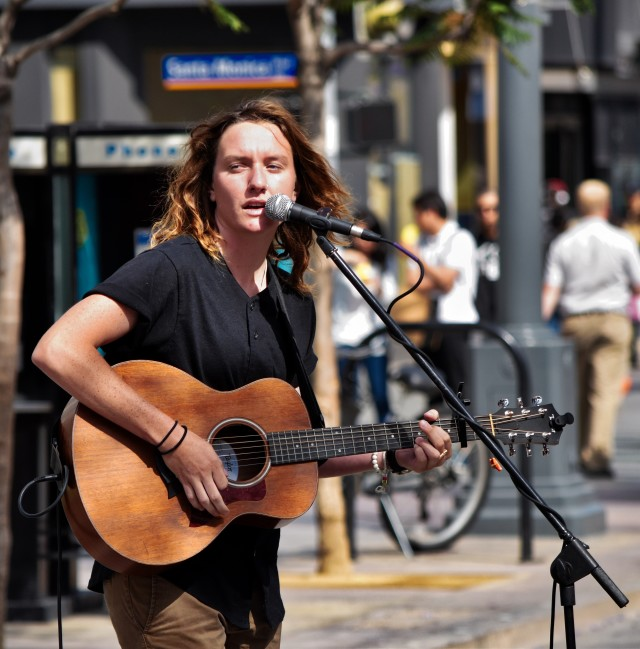 street performer singing and playing a guitar into the microphone on the street at the 3Rd street Promenade in Santa Monica California