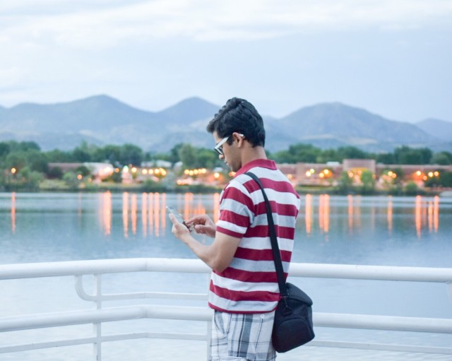 Tourist searching on the phone near a Waterfront reflecting lights in the distance with a mountain backdrop in the twilight.