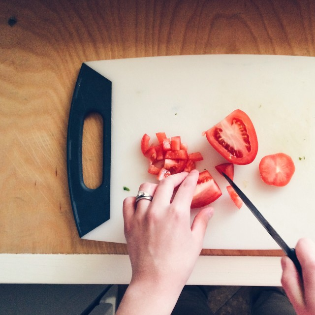 Woman's hands cutting tomatoes.