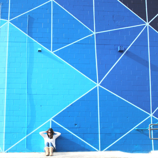 A brunette woman in a white sweater sits in front of a blue geometric wall.