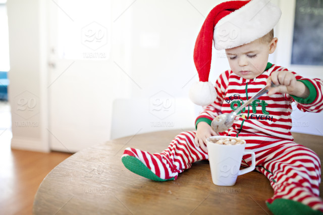 6b47071591bd toddler drinking hot chocolate on the kitchen table while wearing christmas  pajamas and a santa hat. winter ...
