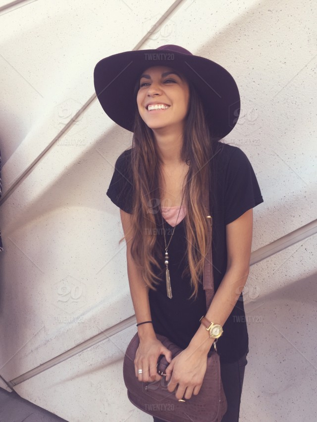 A Young Lady Wearing A Stylish Hat Is Leaning Against A Wall