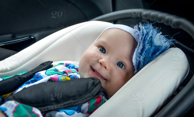 Smiling Baby Girl With Hairband In The Infant Car Seat Stock Photo
