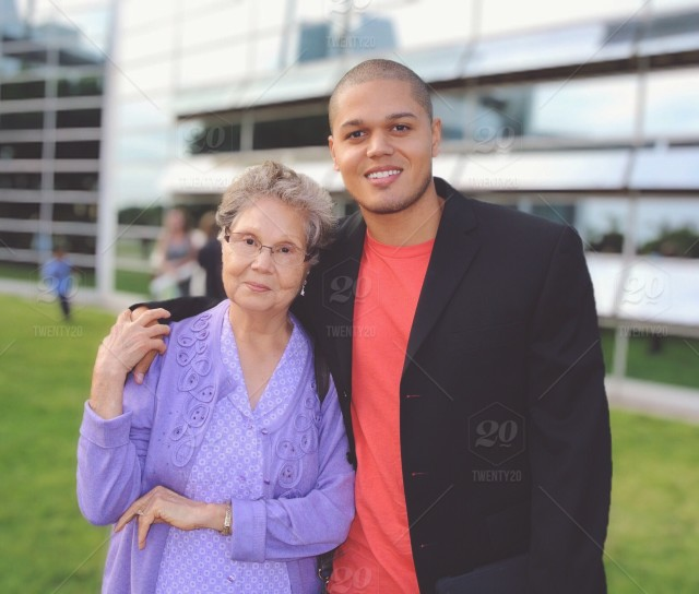 a grandson is side hugging his grandma for a picture stock photo