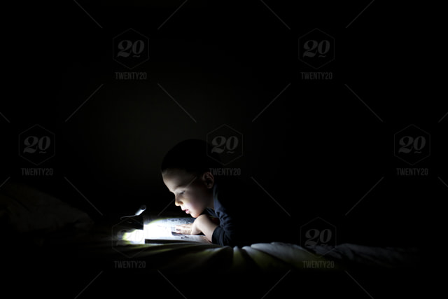 Boy reading books in bed by book light in a dark room stock photo ...