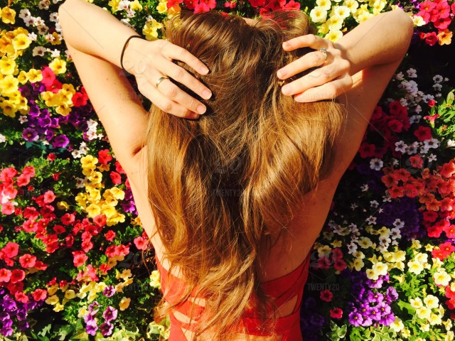 Back Of Woman With Long Dark Blonde Hair Surrounded By Wall Of