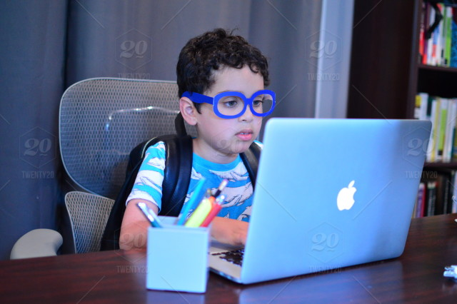 Kid Pretending To Be A Nerd Coding On The Computer Stock Photo