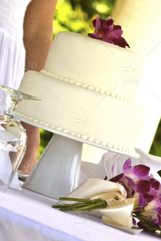 White Wedding Cake With Purple Orchid In Jamaica Stock Photo
