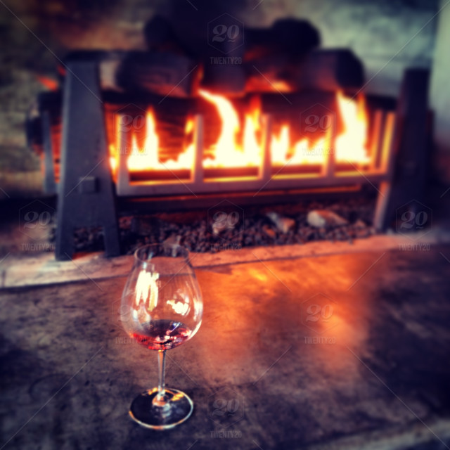 Wine glass by the fireplace stock photo 49422da1-506d-4c93