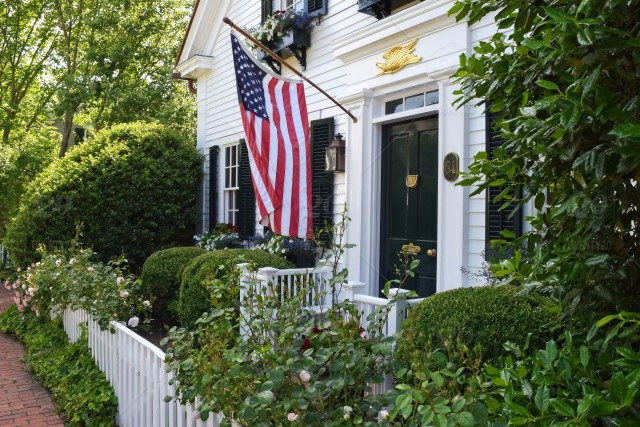 American Flag Hanging Out In Front Of A White Clapboard House With A