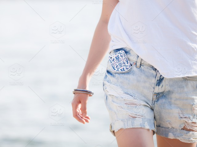 56b7d9245c20 Girl in denim shorts and white T-shirt stock photo f4eb0f51-699e-4d03 ...