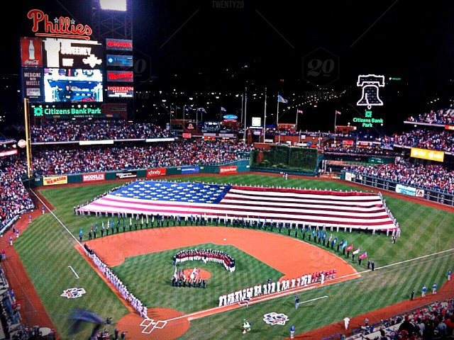 A large American Flag displaying on a baseball field stock