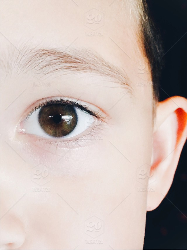 Close up view of young child's face with left eye staring at camera in