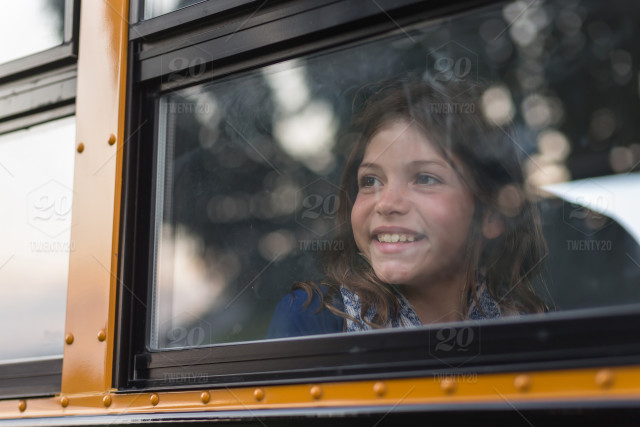 Happy young girl looks out the window of a school bus stock photo  8798352a-1309-440c-8c21-e8d2856bdc4f