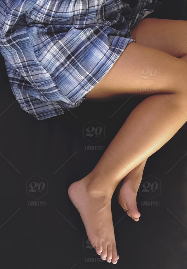 Looking down at woman in a short blue plaid dress with bare legs and ...