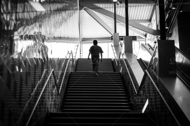 Silhouette of a young man climbing stairs inside ...